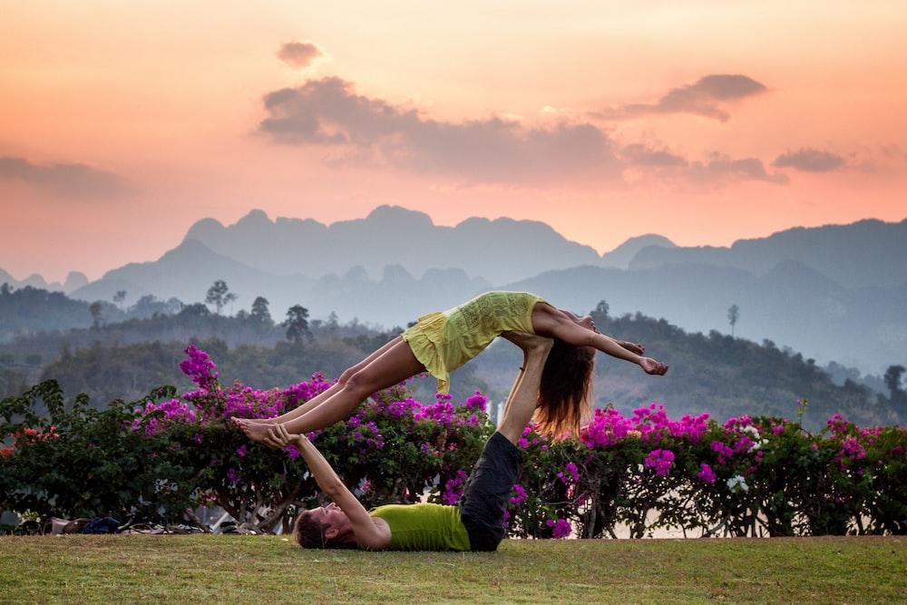 man and woman doing couple yoga