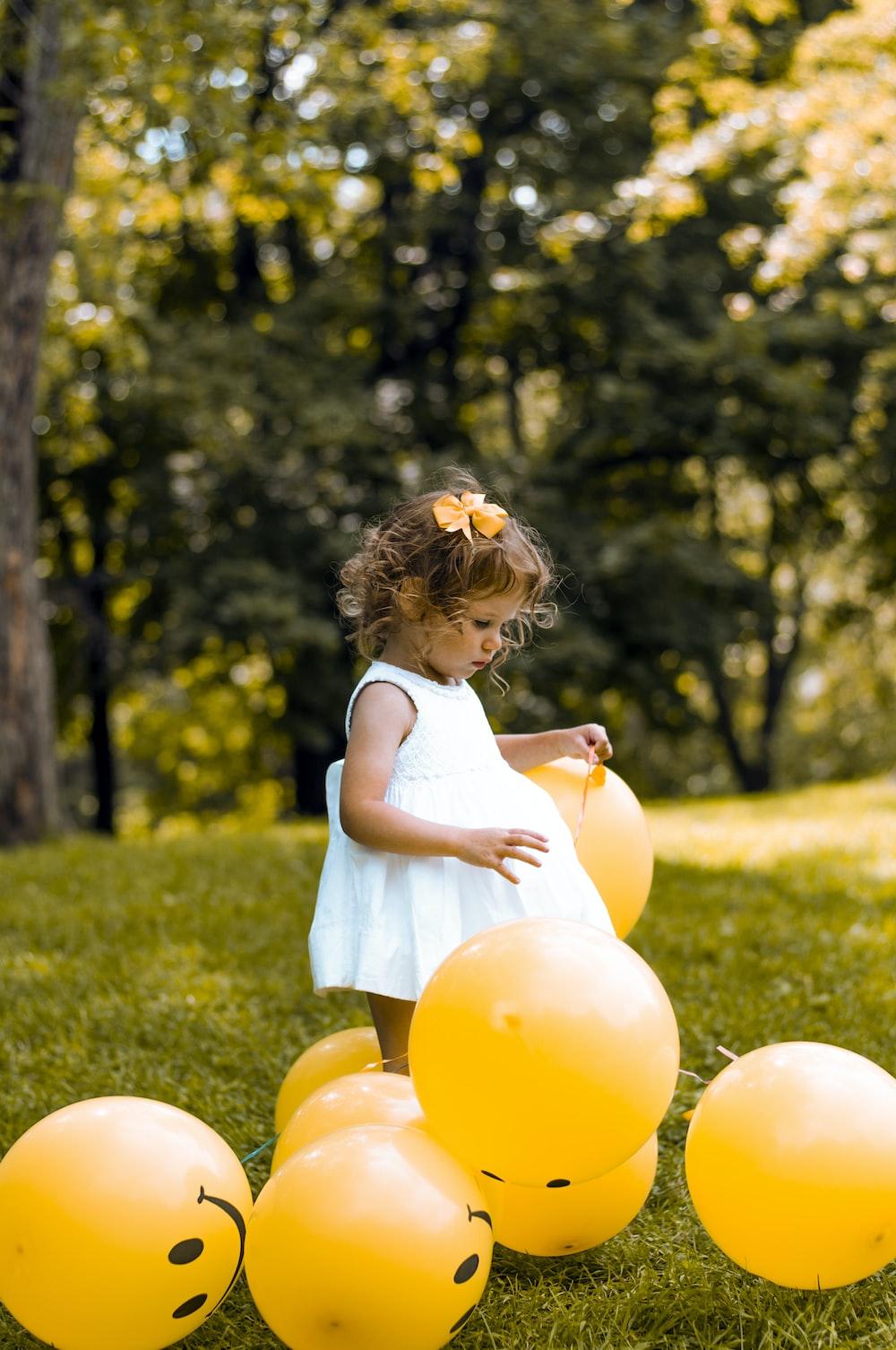 girl wearing white sleeveless dress beside balloons