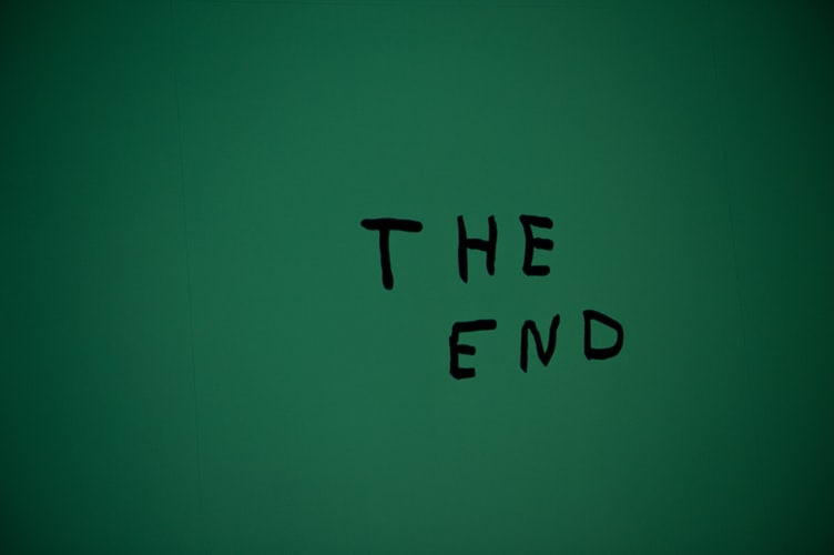 "A green wall with the words ""The End"" written in black felt marker on it."