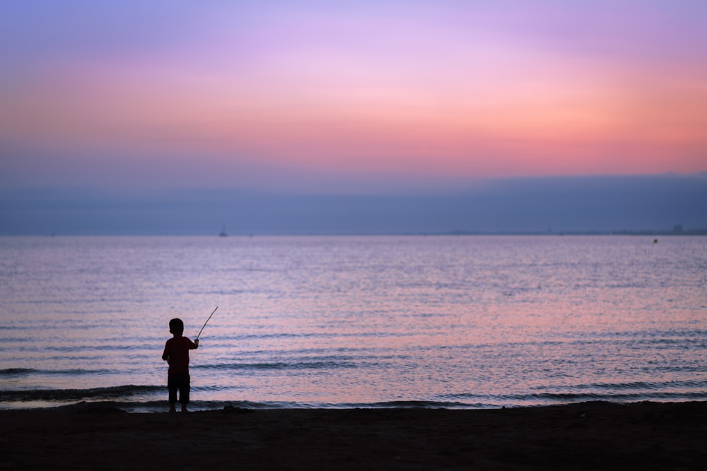 silhouette photography of toddler fishing on body of water