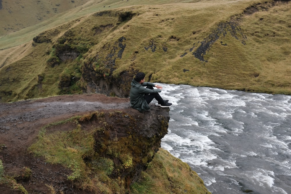 man sit on mountain near body of water