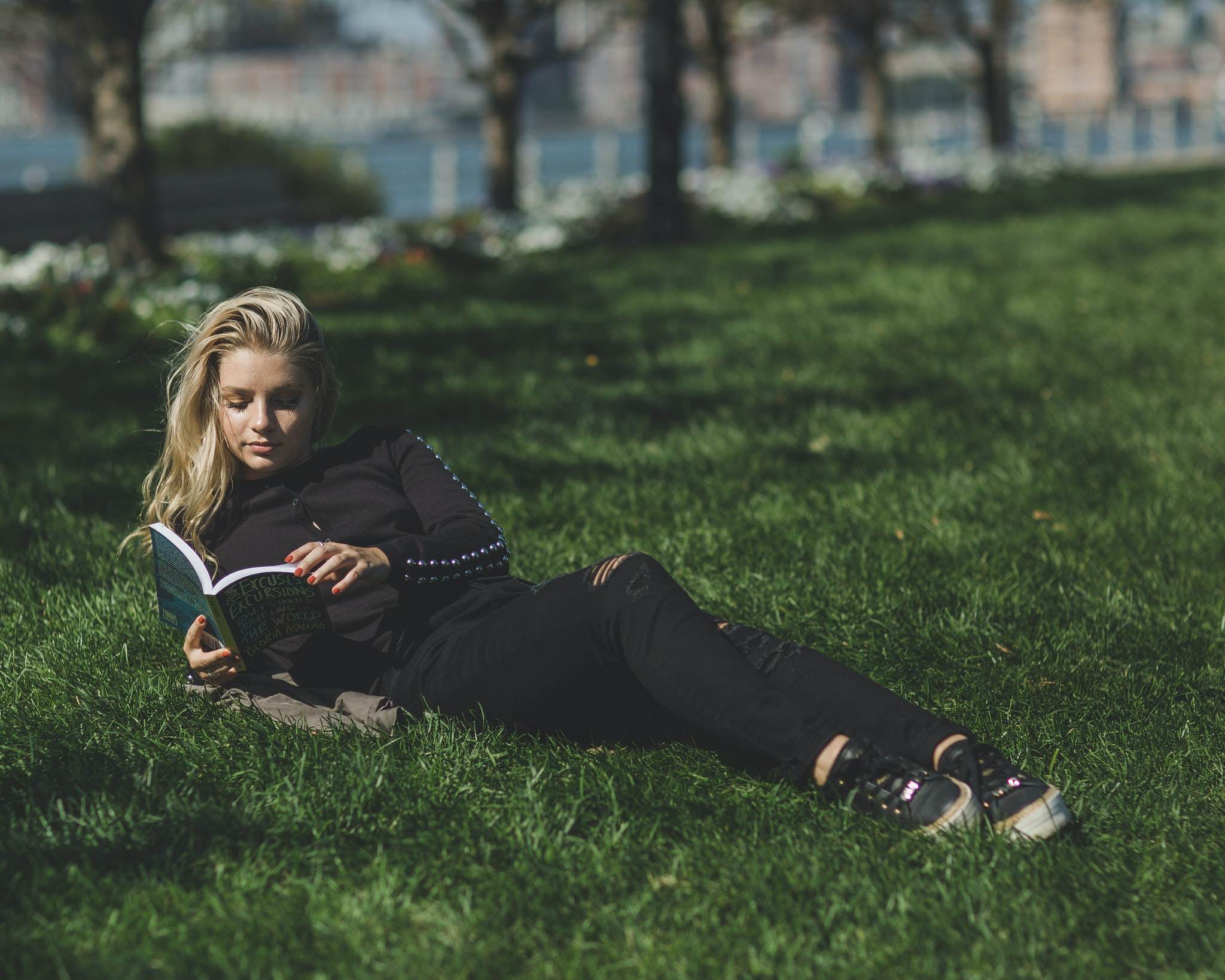 woman reading book leaning on green grass field