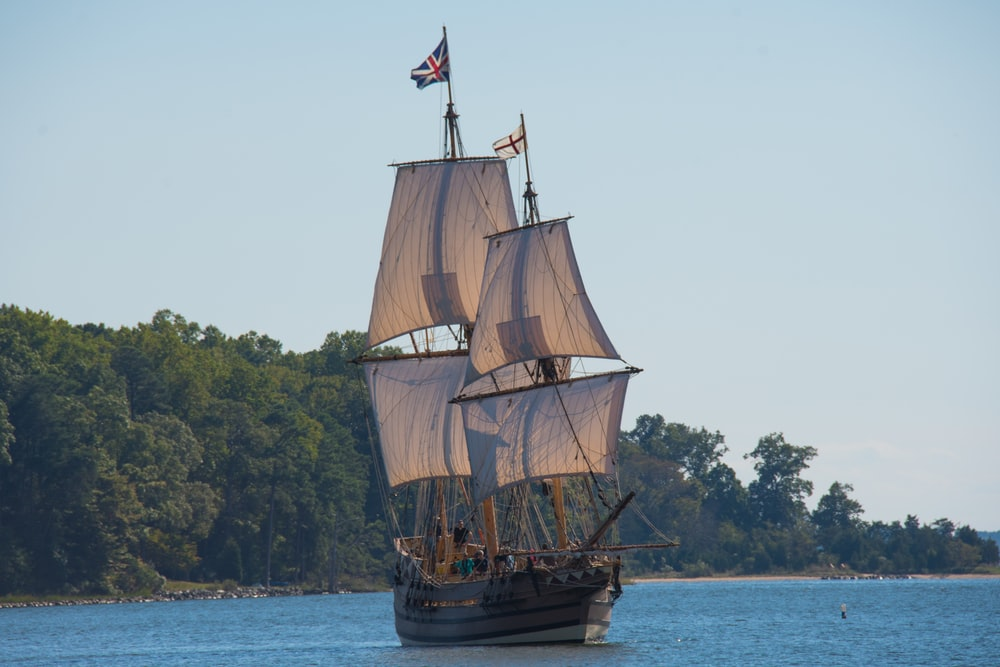 brown galleon ship on body of water near trees