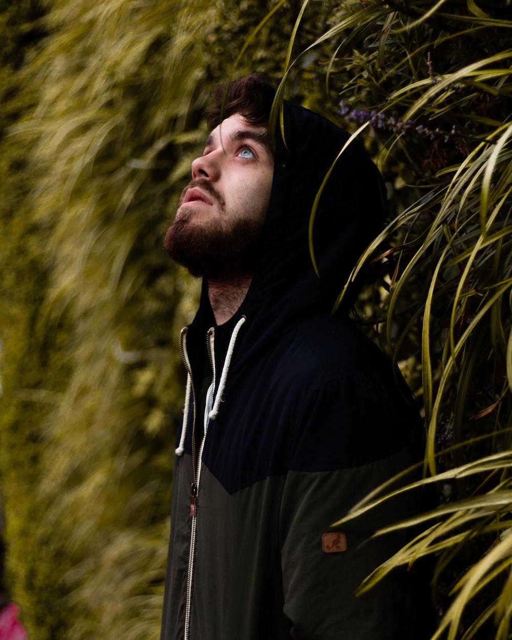 man wearing black zip-up hoodie looking up