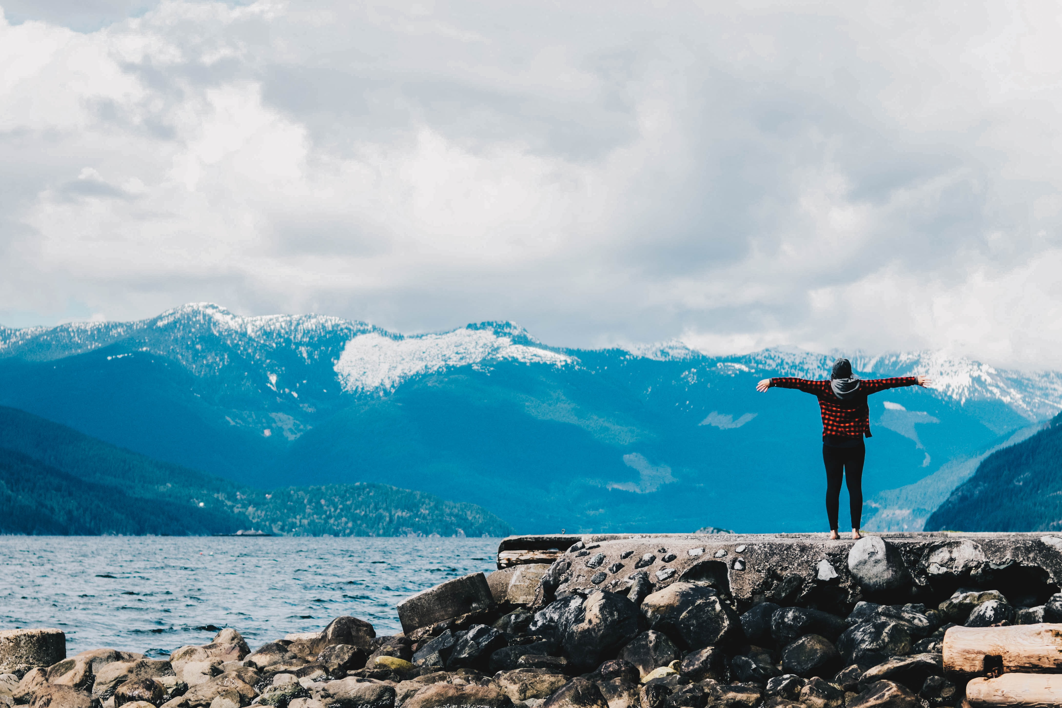 person spreading arms near water and mountain range