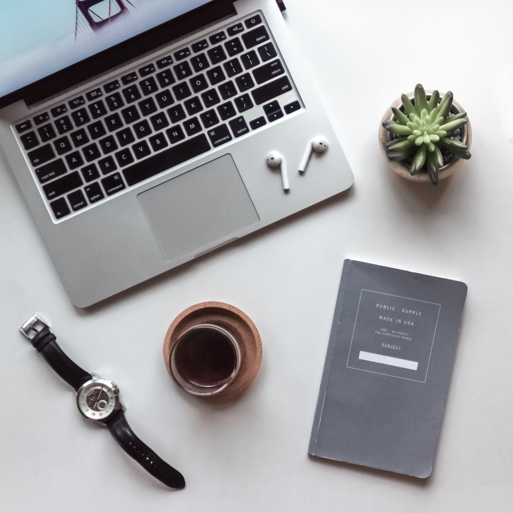 flat-lay photography of MacBook, coffee-filled cup, book, and wristwatch