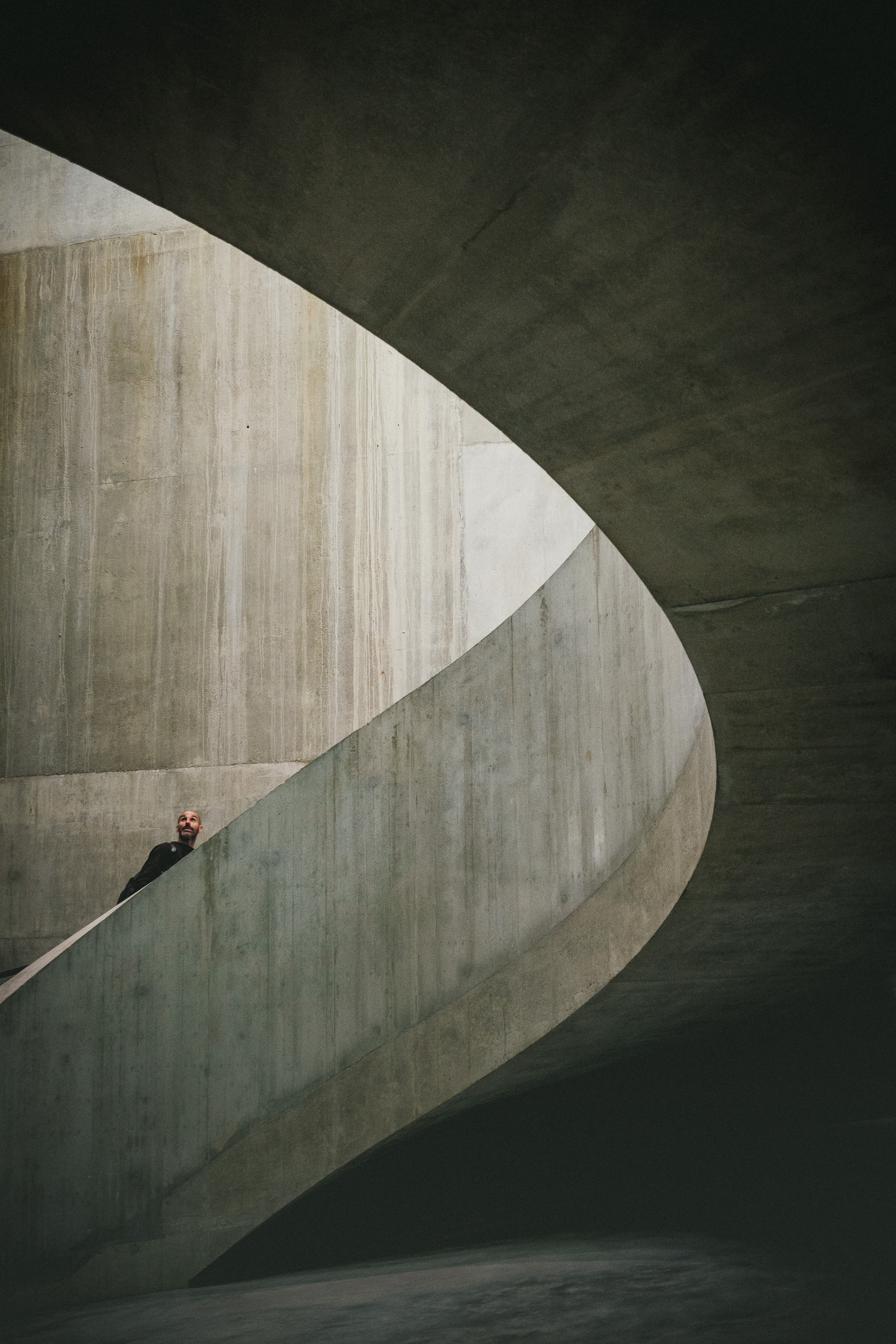 photography of man climbing a spiral stairs