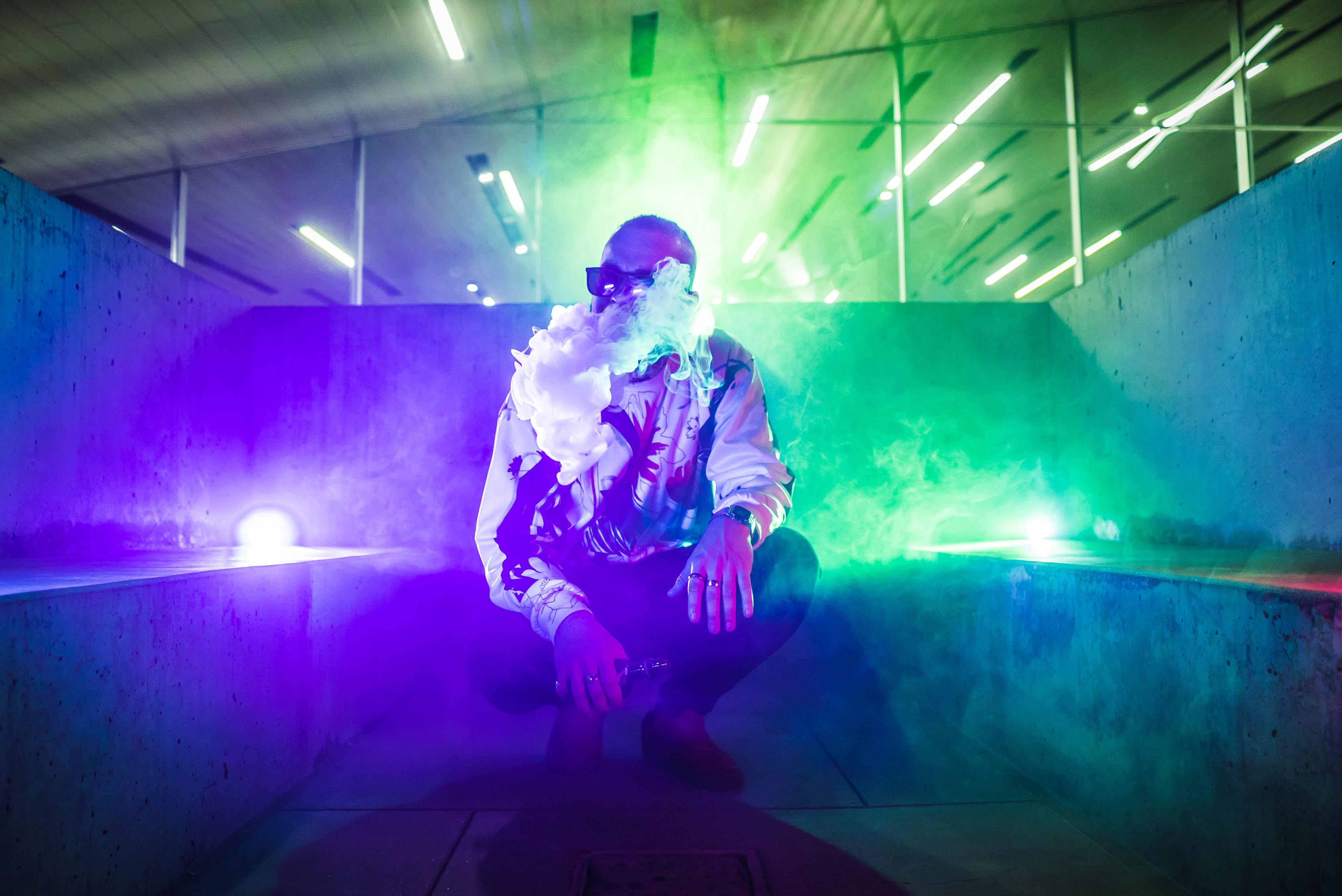 man with vape smoke squatting on ground