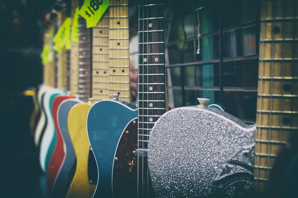 assorted-color guitar hang on metal rack