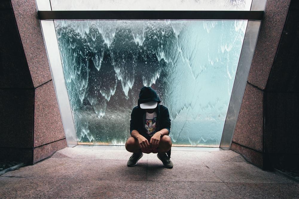 person sitting near glass window