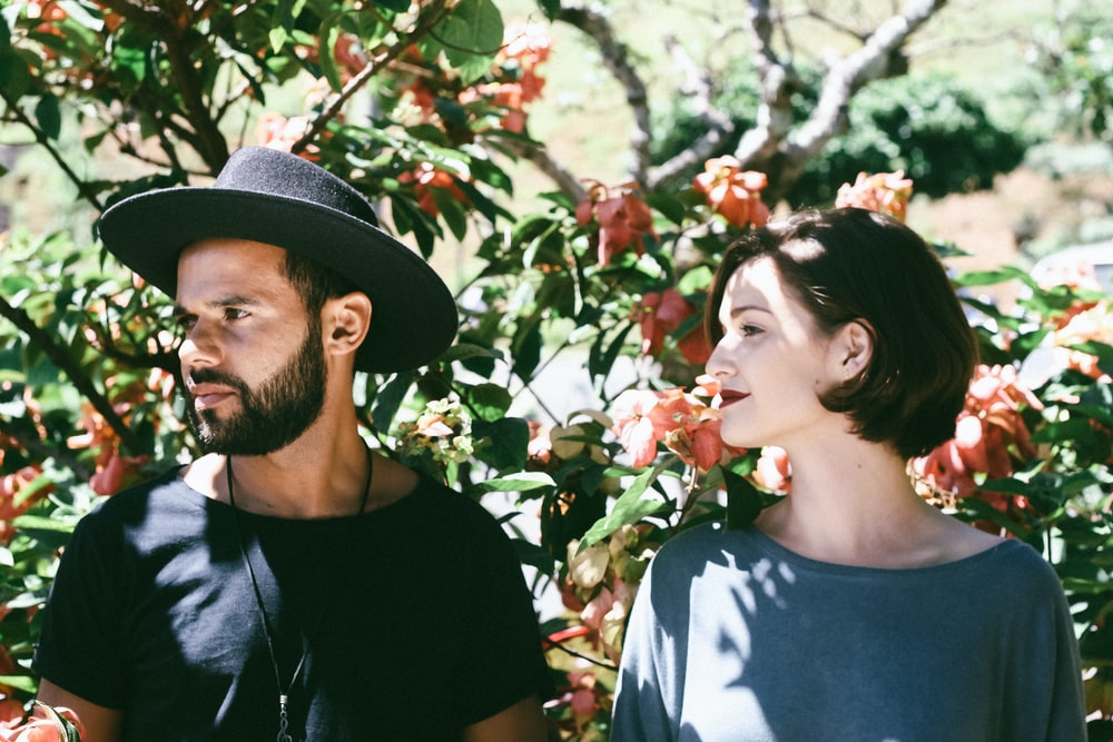 woman standing beside man wearing black hat