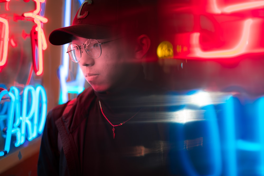 man standing near red and blue neon signages