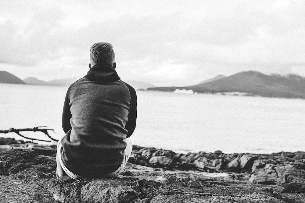 man in black hoodie sitting on rock near body of water during daytime