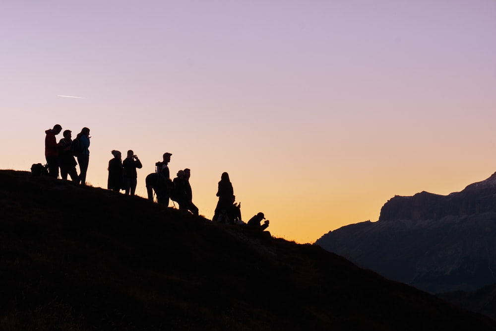 silhouette of group of people on hill