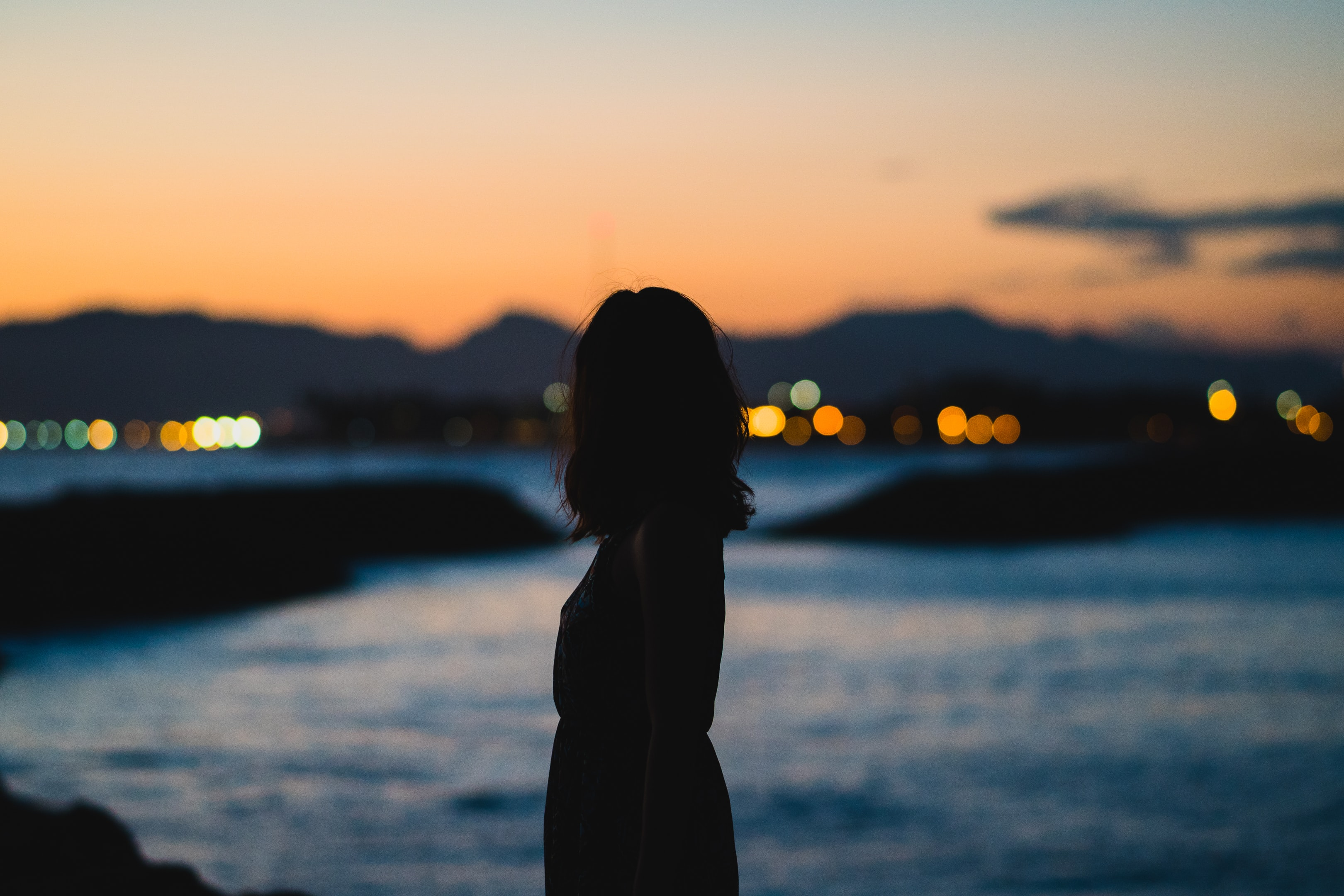 silhouette of woman standing beside body of water