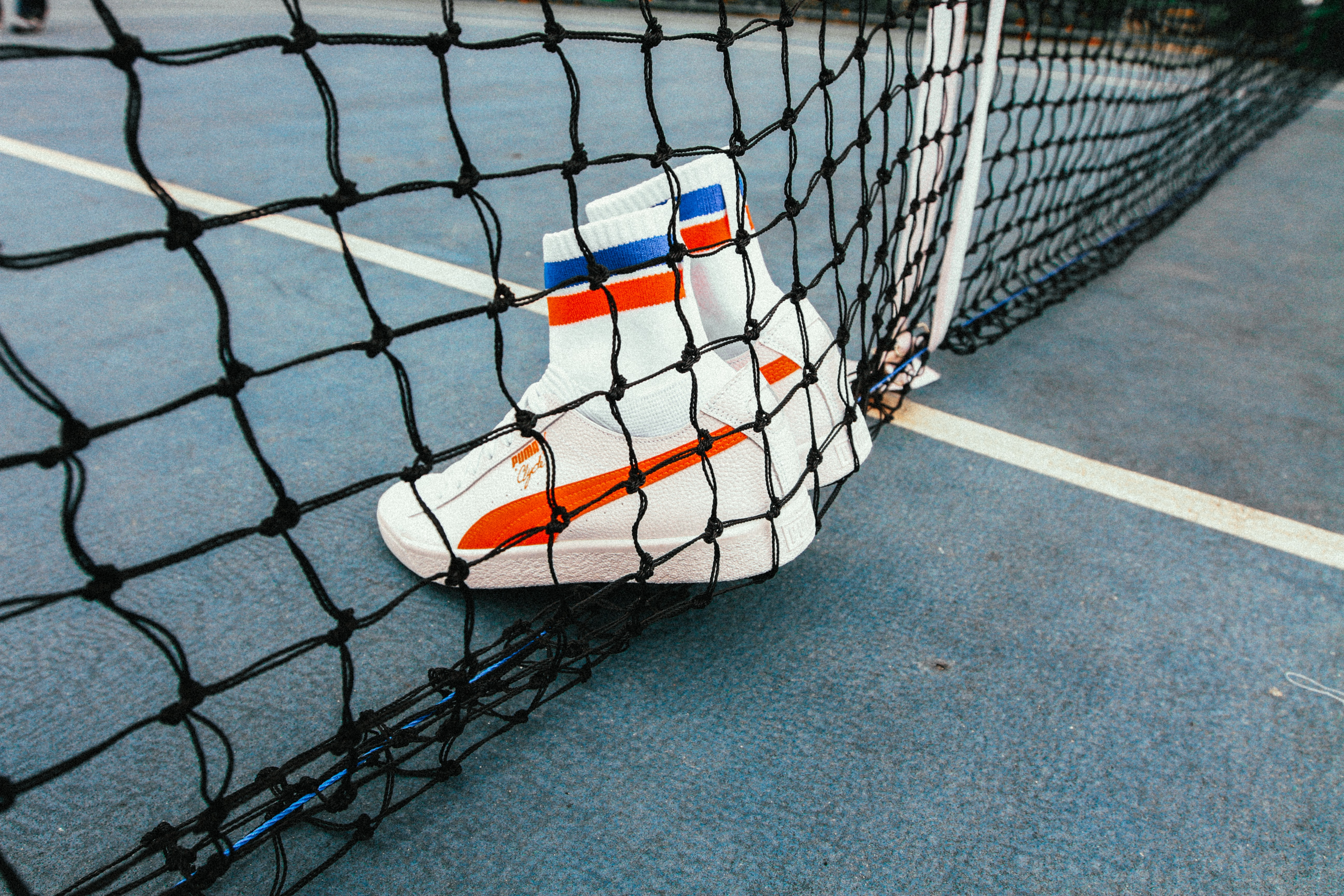 white-and-red Puma Sock shoes on tennis net