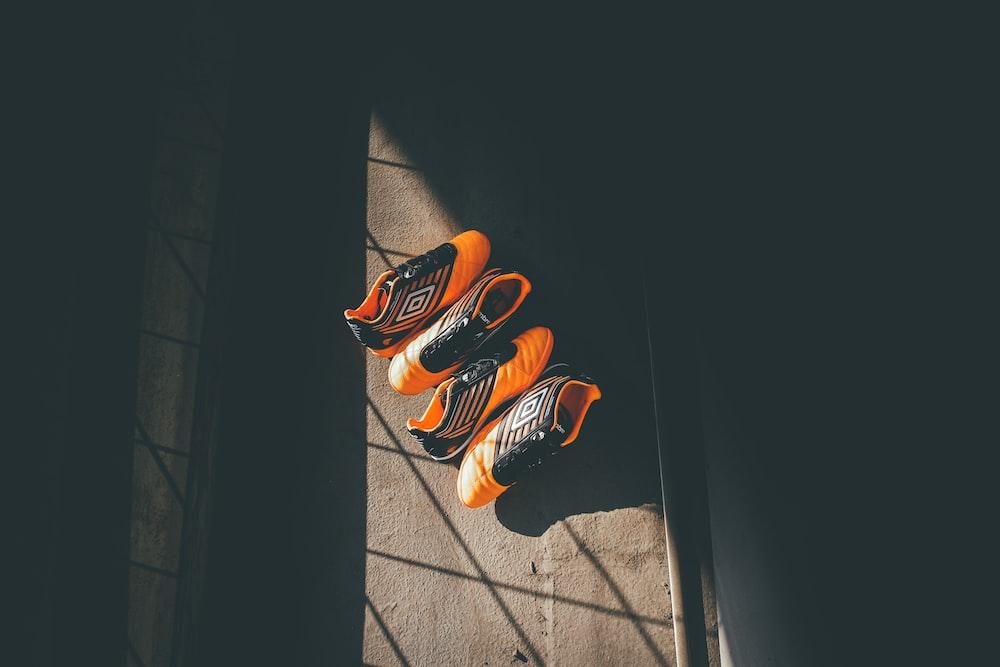 two pairs orange-and-black Umbro shoes