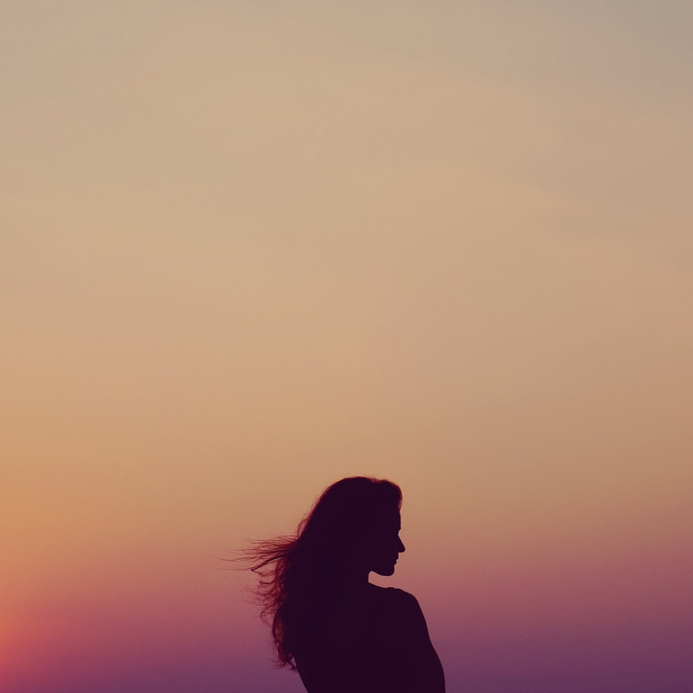silhouette of woman under orange sky