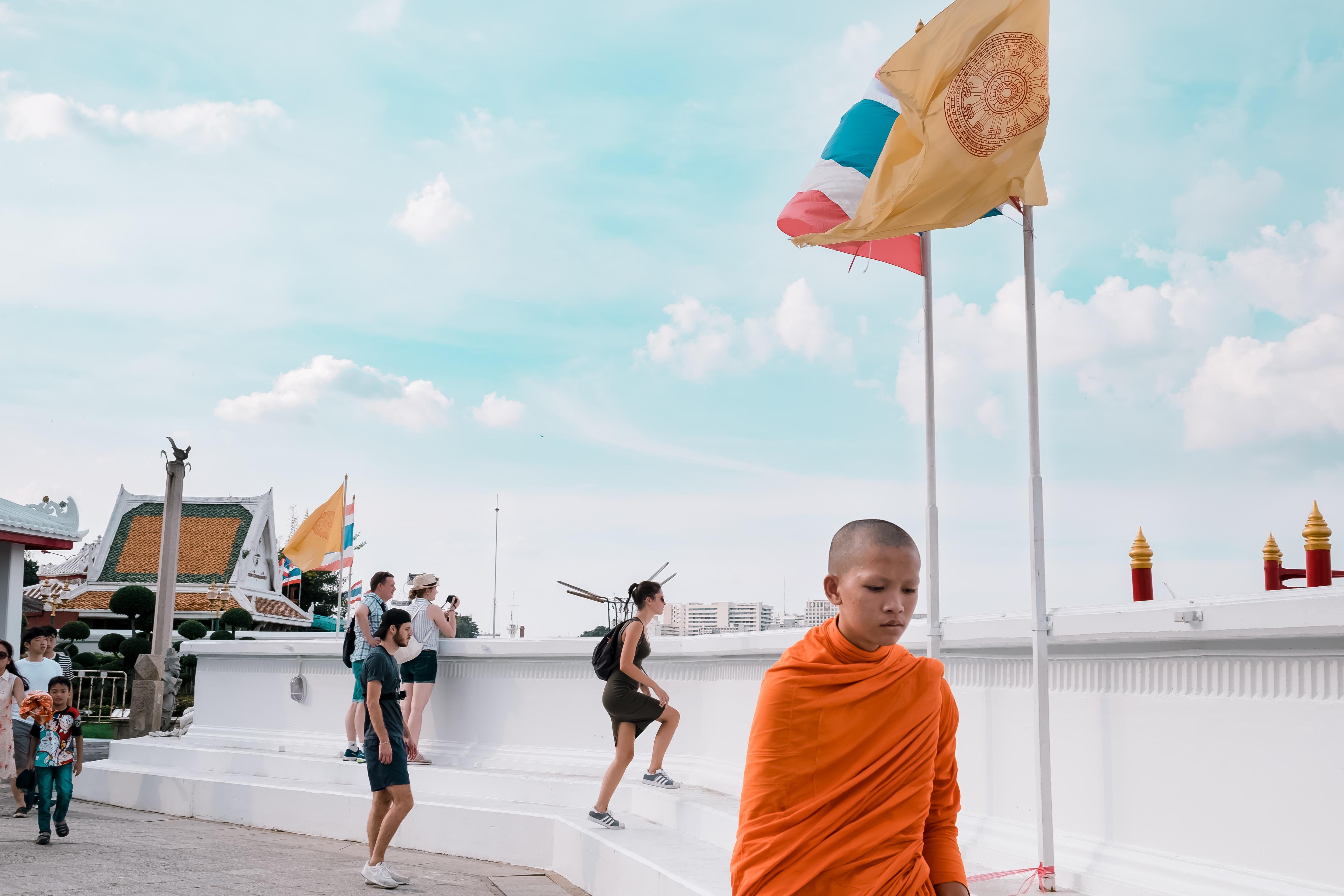 monk standing near white wall