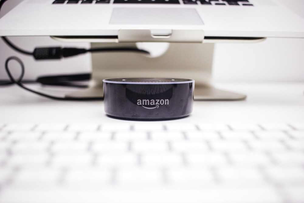 Amazon Echo Dot near laptop on stand
