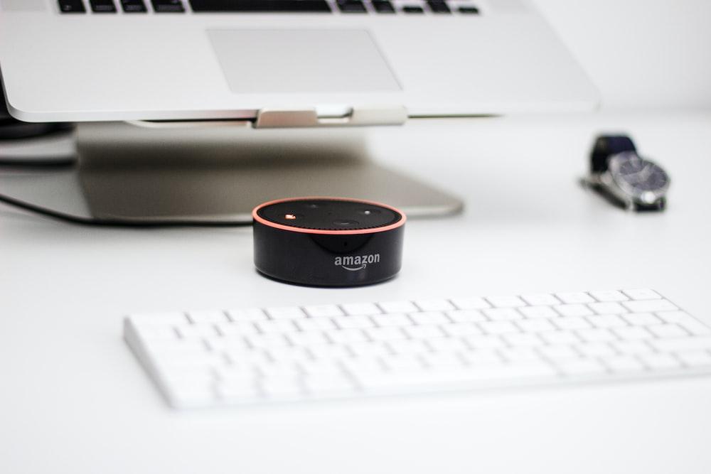 black Amazon Echo Dot speaker beside Apple Magic Mouse