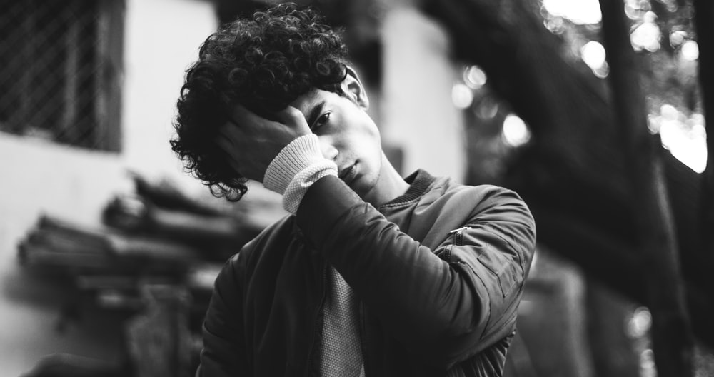 grayscale photo of man in jacket putting his palm on his forehead