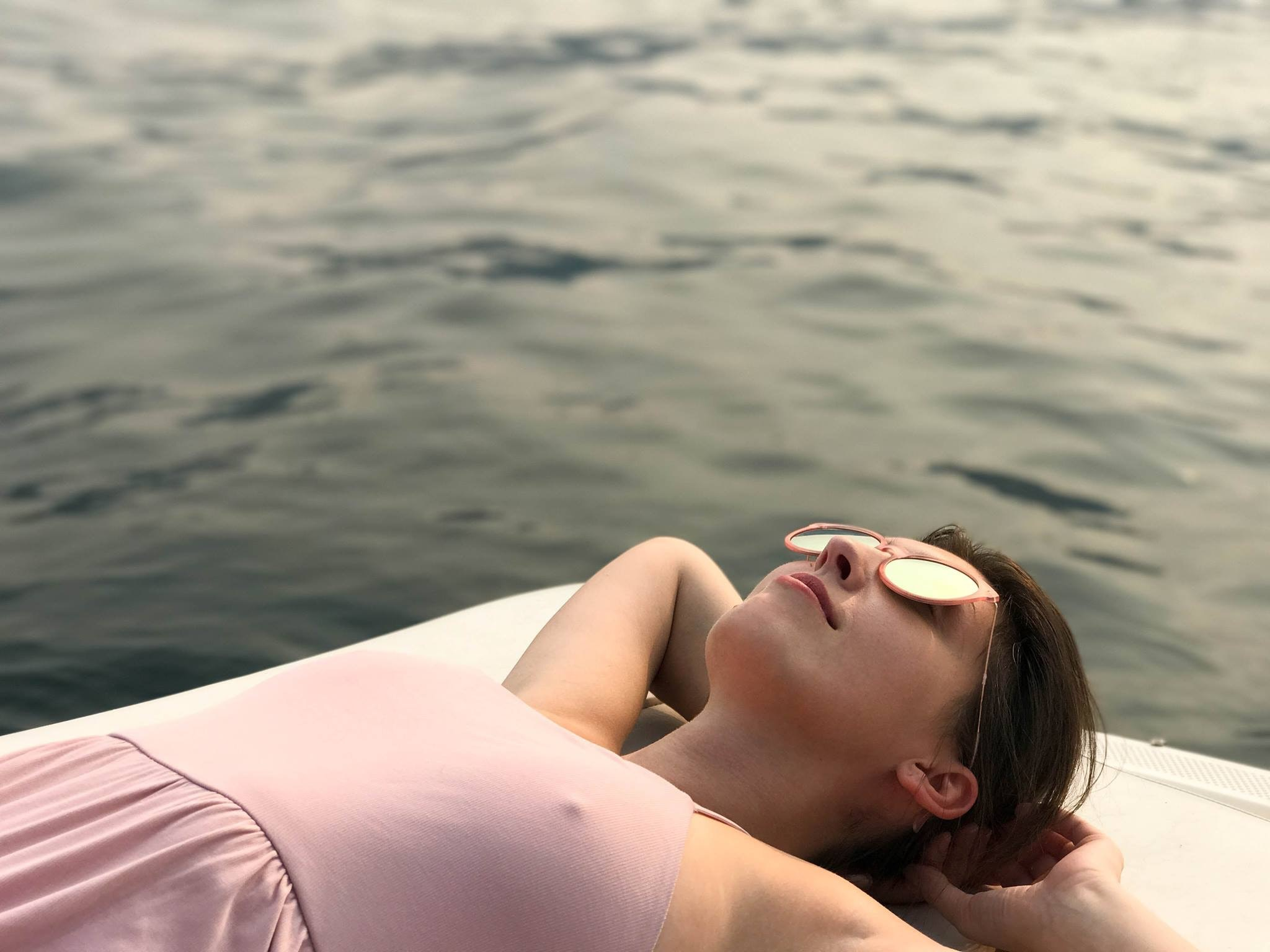 woman laying on white surface near body of water
