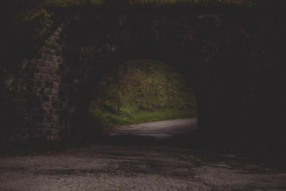 gray road in black concrete brick tunnel