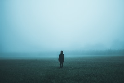 person standing on misty ground fog teams background