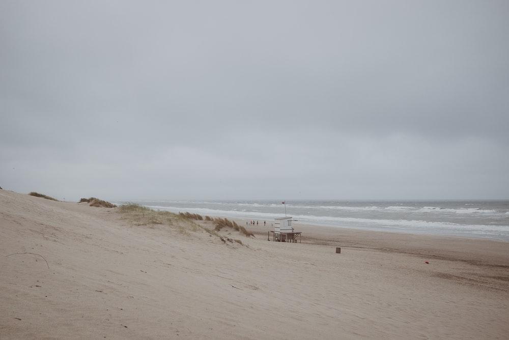 white life guard tower near sea under gray sky