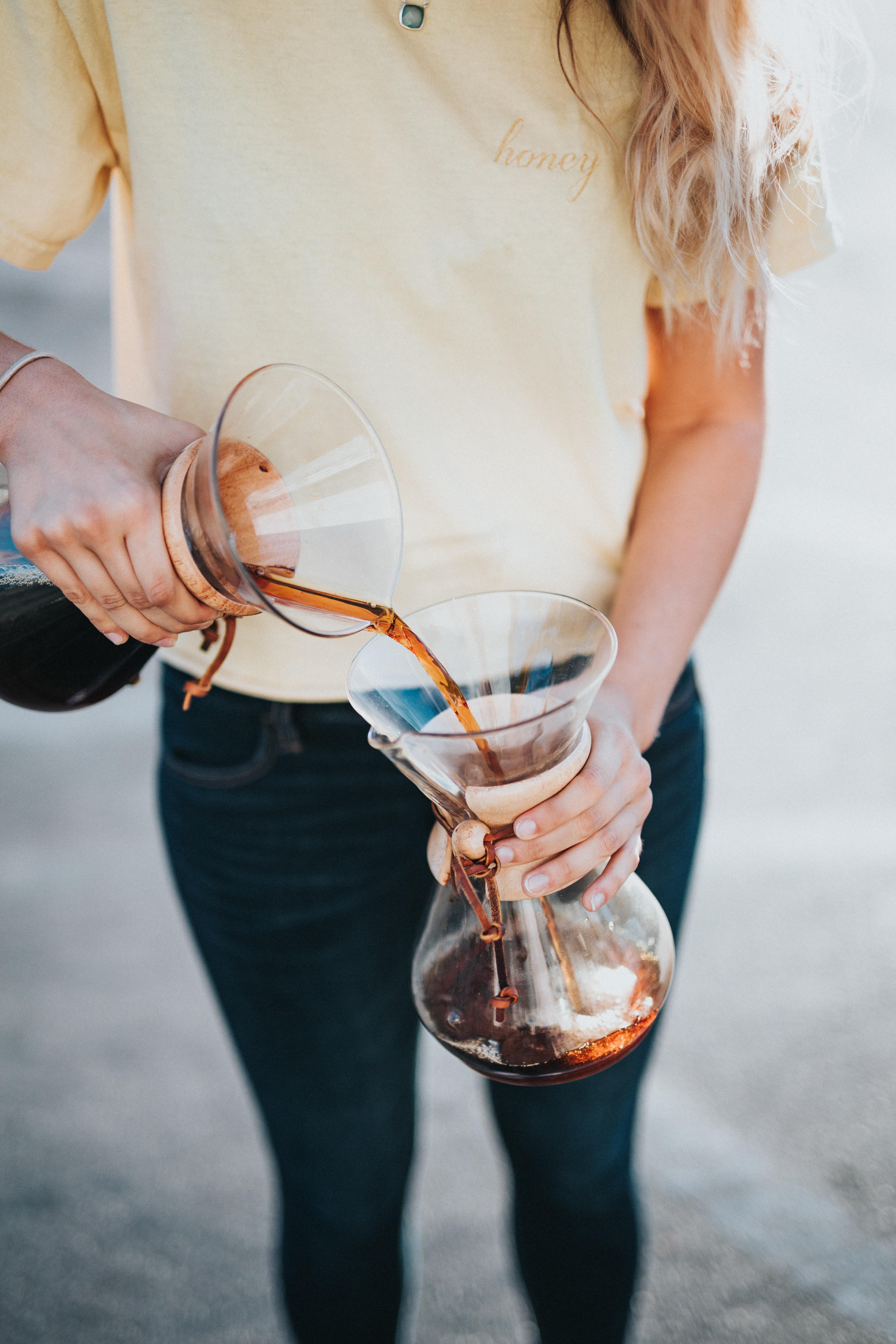 woman pouring liquid on jar
