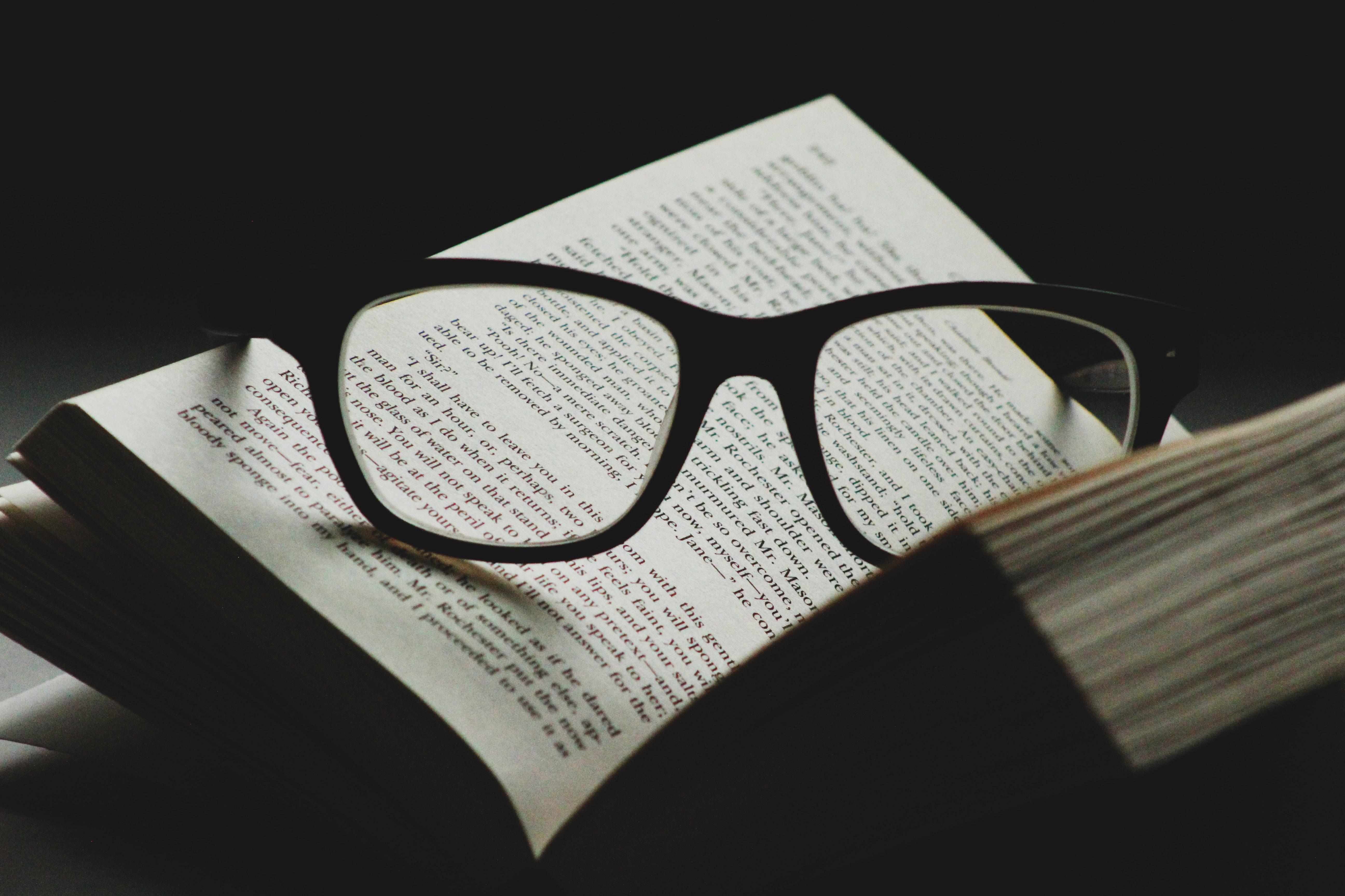 black framed eyeglasses on top of open book