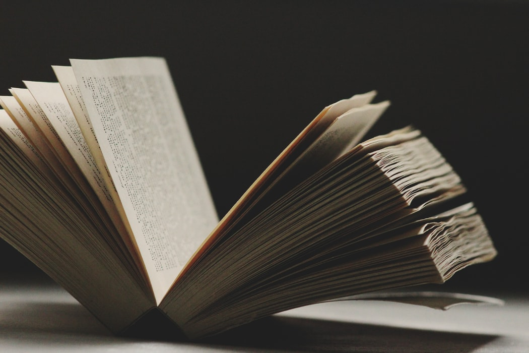 A long and old looking book on a black background.