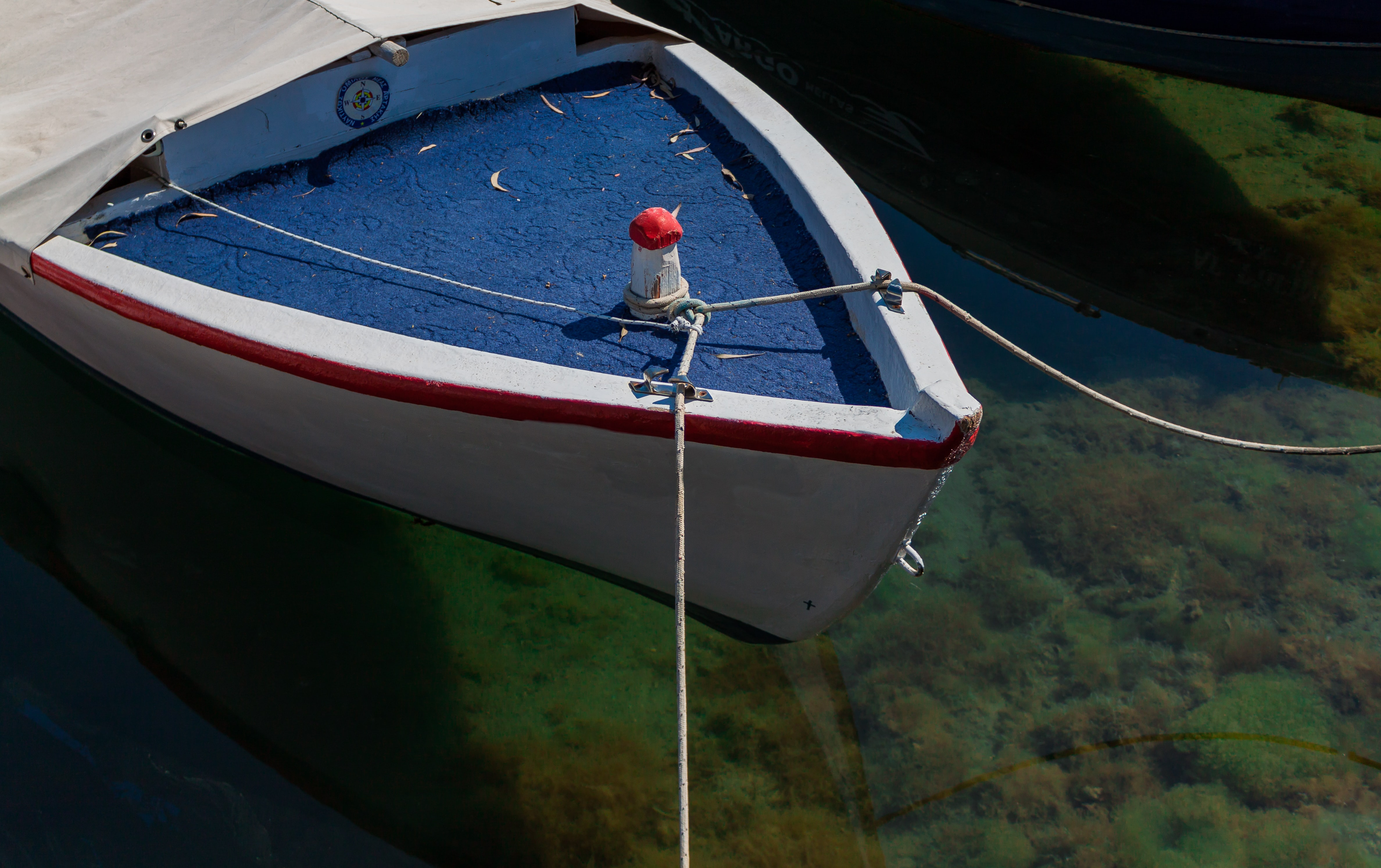 white and blue wooden boat with rope closeup photography
