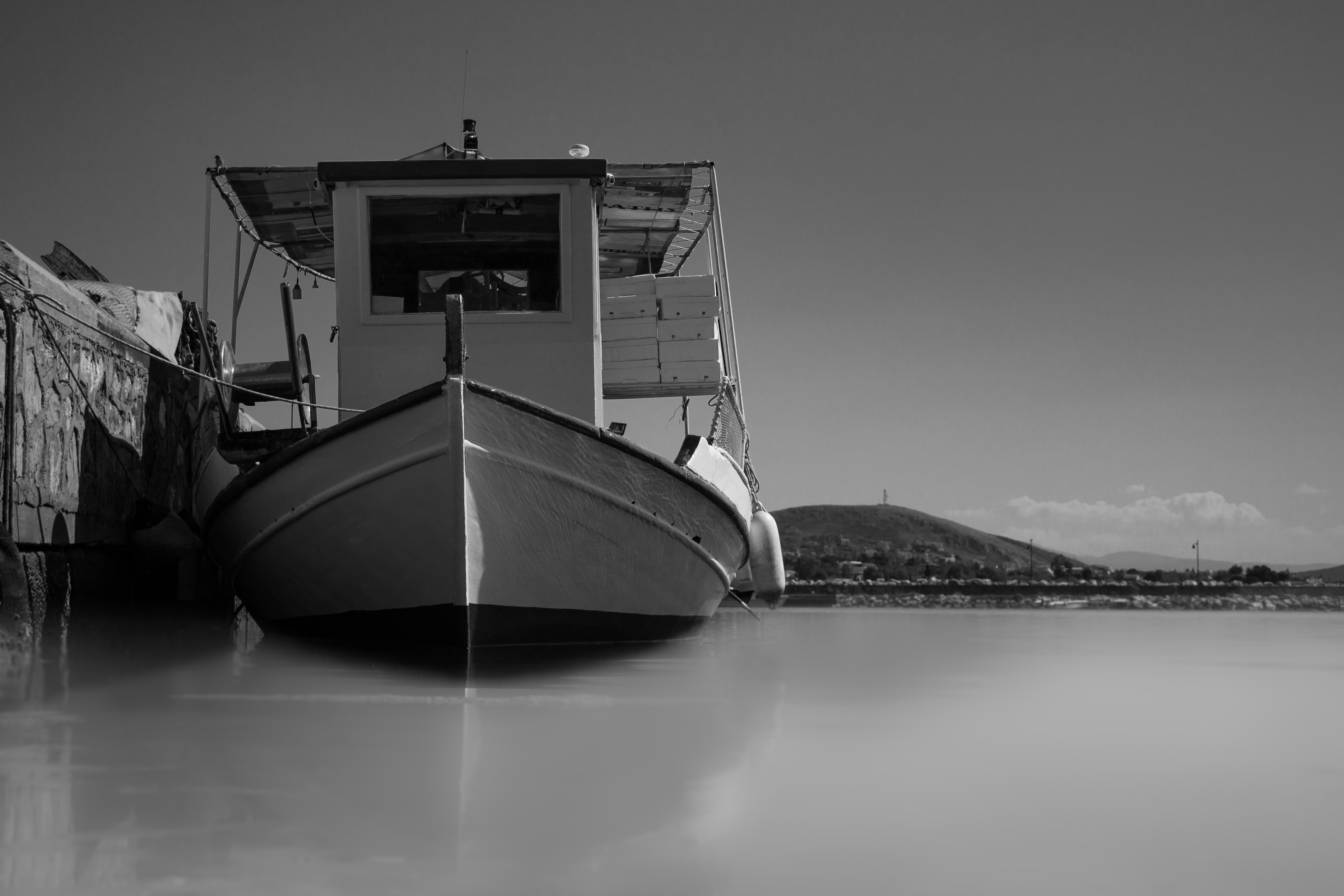 grayscale photography of boat near dock