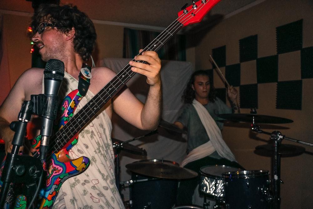 man playing guitar wearing one-shoulder dress inside room