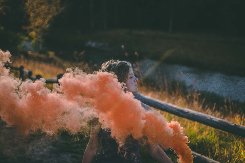 woman playing red smoke near river