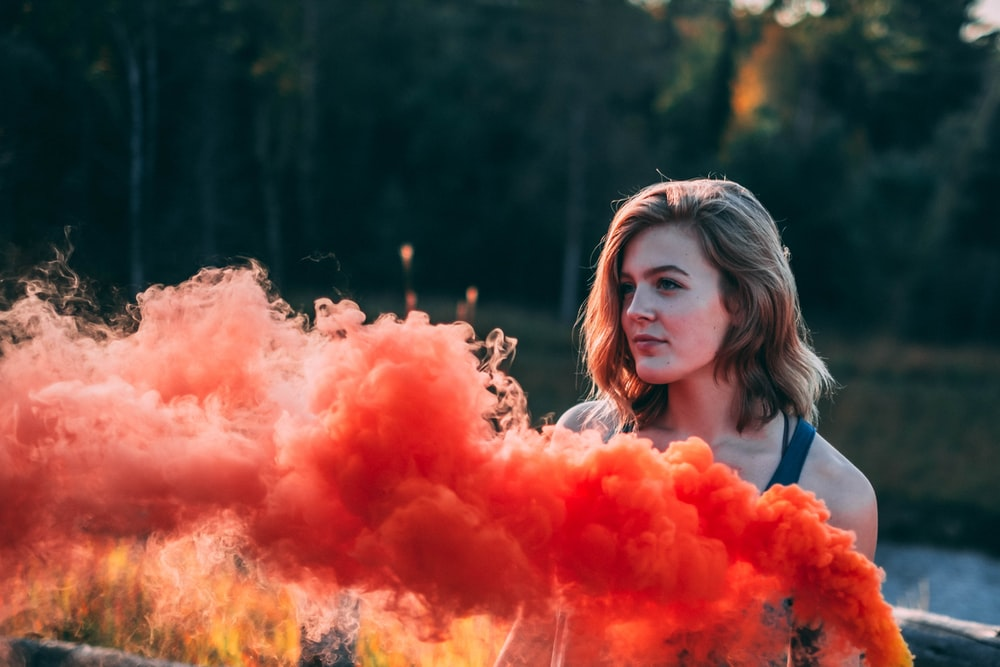 woman standing in front of flare smoke