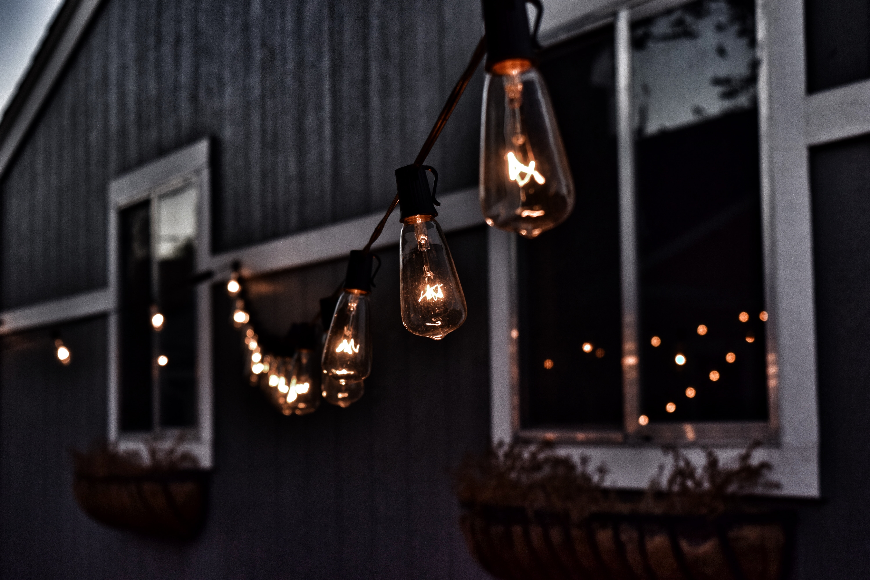 piled hanging lighted bulb beside house