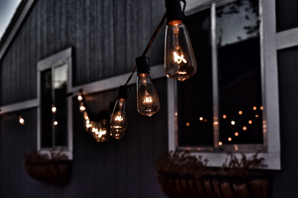 piled hanging lighted bulb beside house