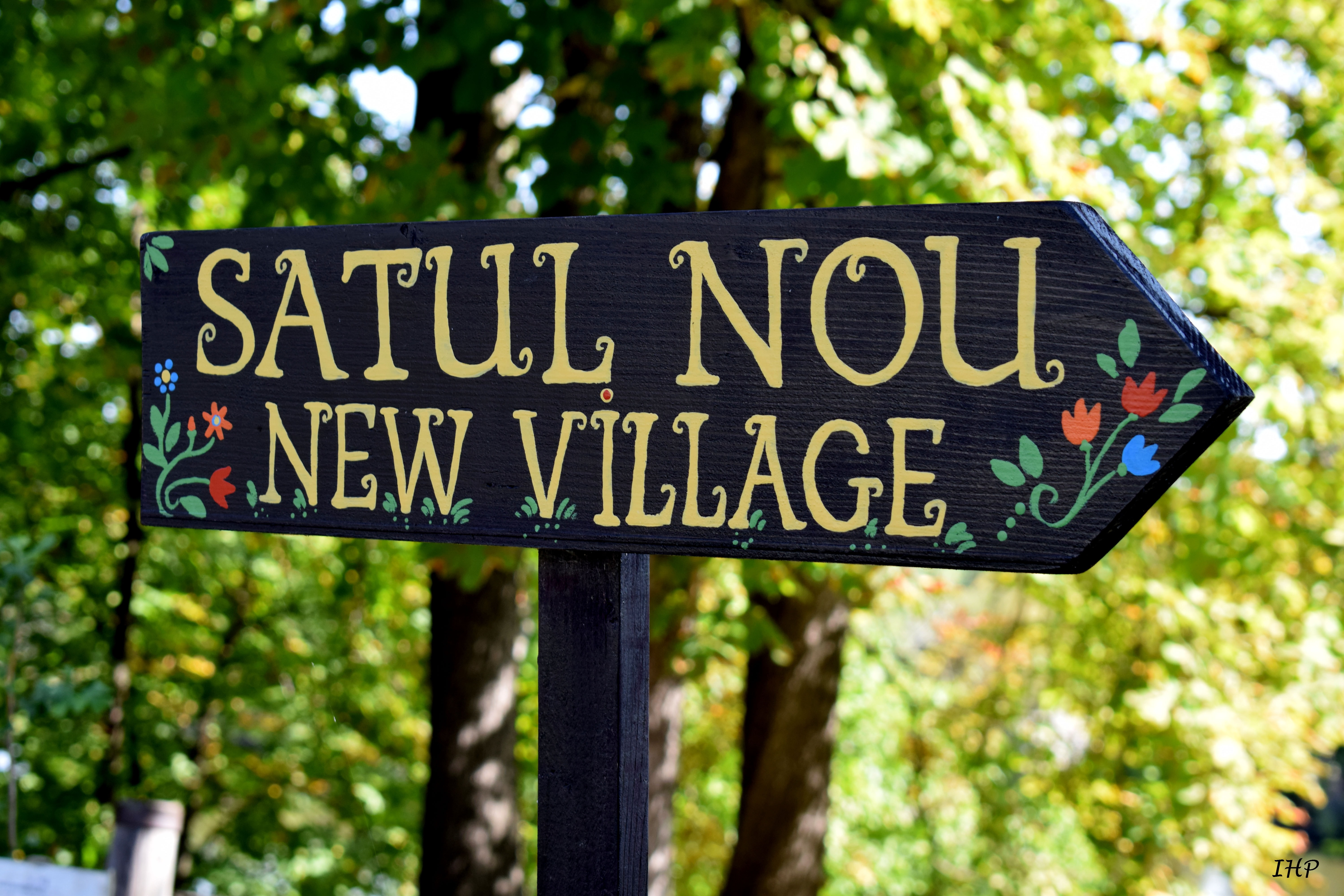 Satul Nou New Village signage under green trees