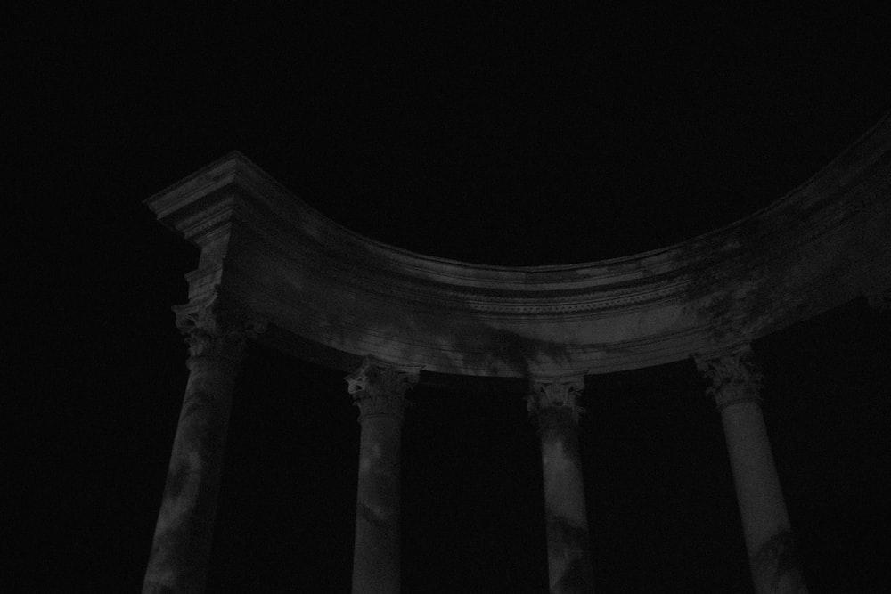 white concrete pillar stand building under night sky