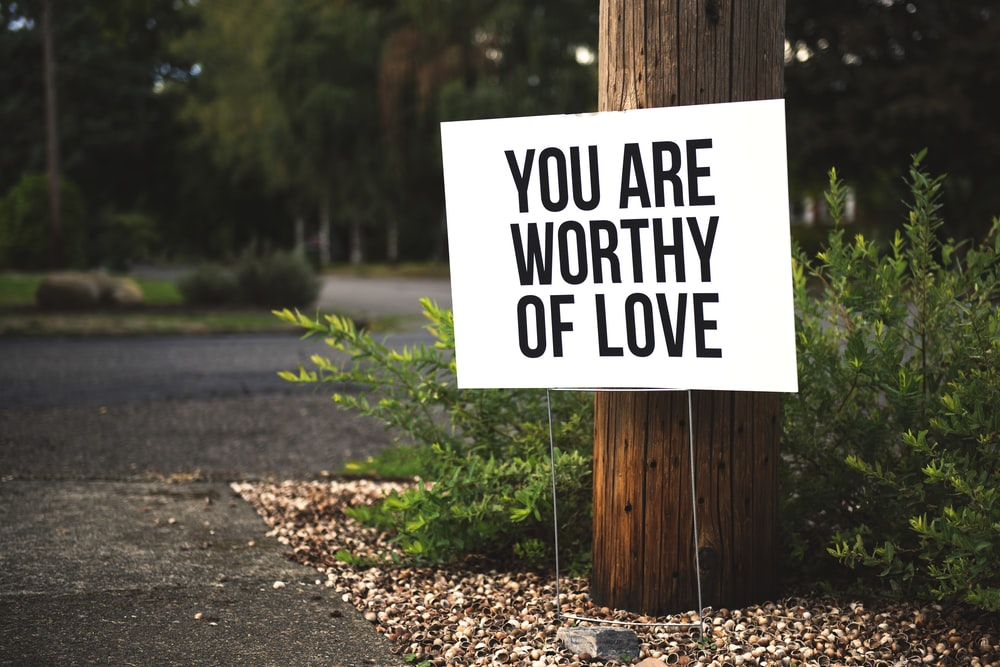 you are worthy of love sign beside tree and road