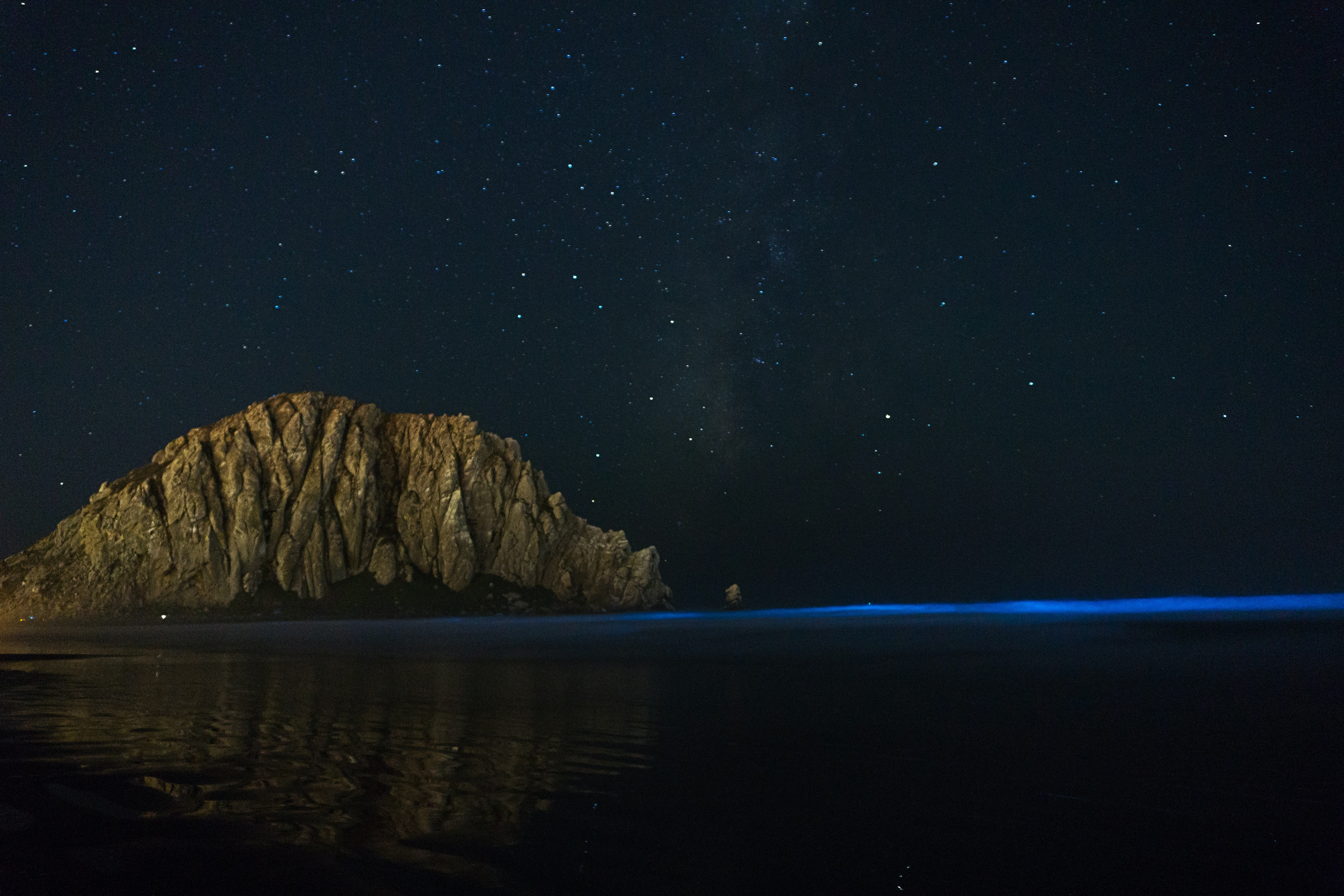 gray rock formation near sea at nighttime