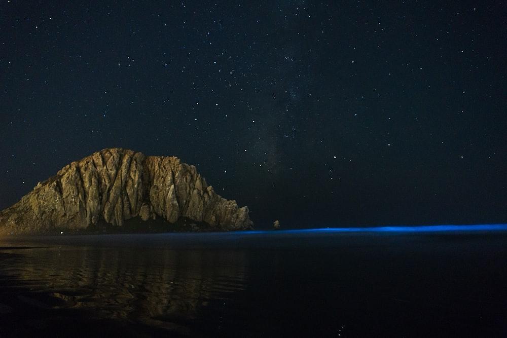 gray rock formation near sea at nighttime