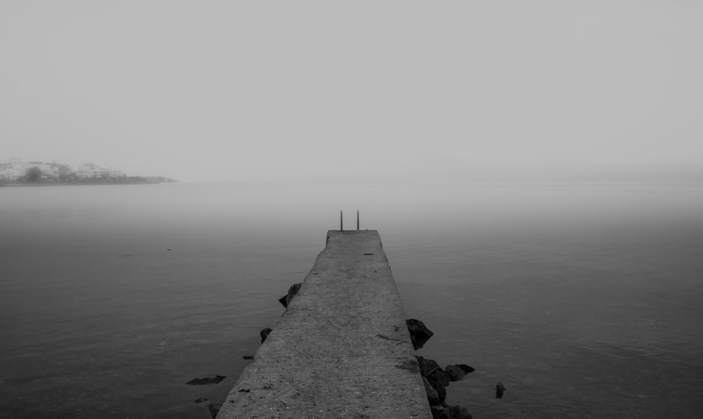 grayscale photography of concrete beach dock
