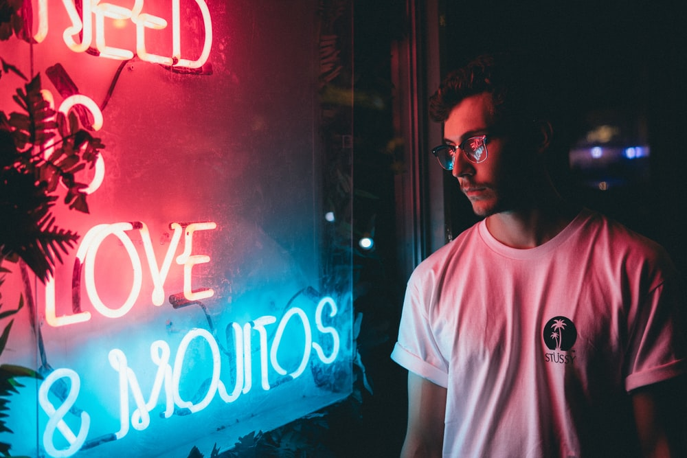man standing near red and blue neon signage
