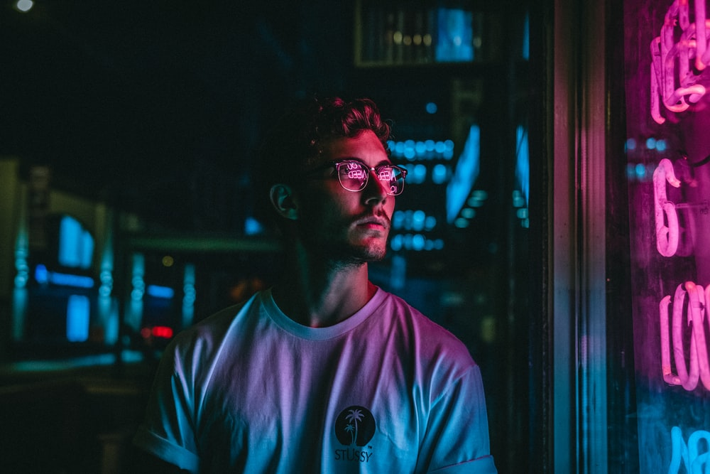 man looking at glass storefront windowpane during night