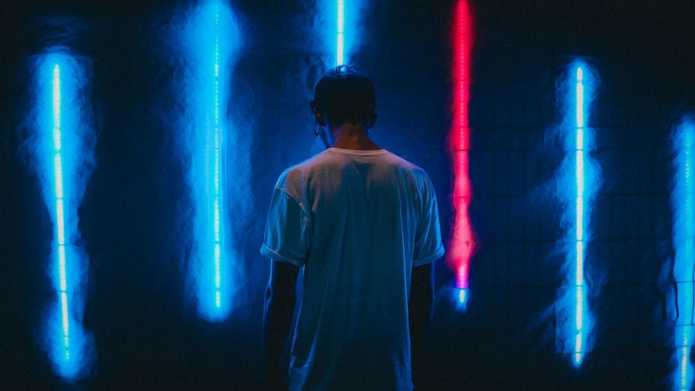man standing near blue LED strips