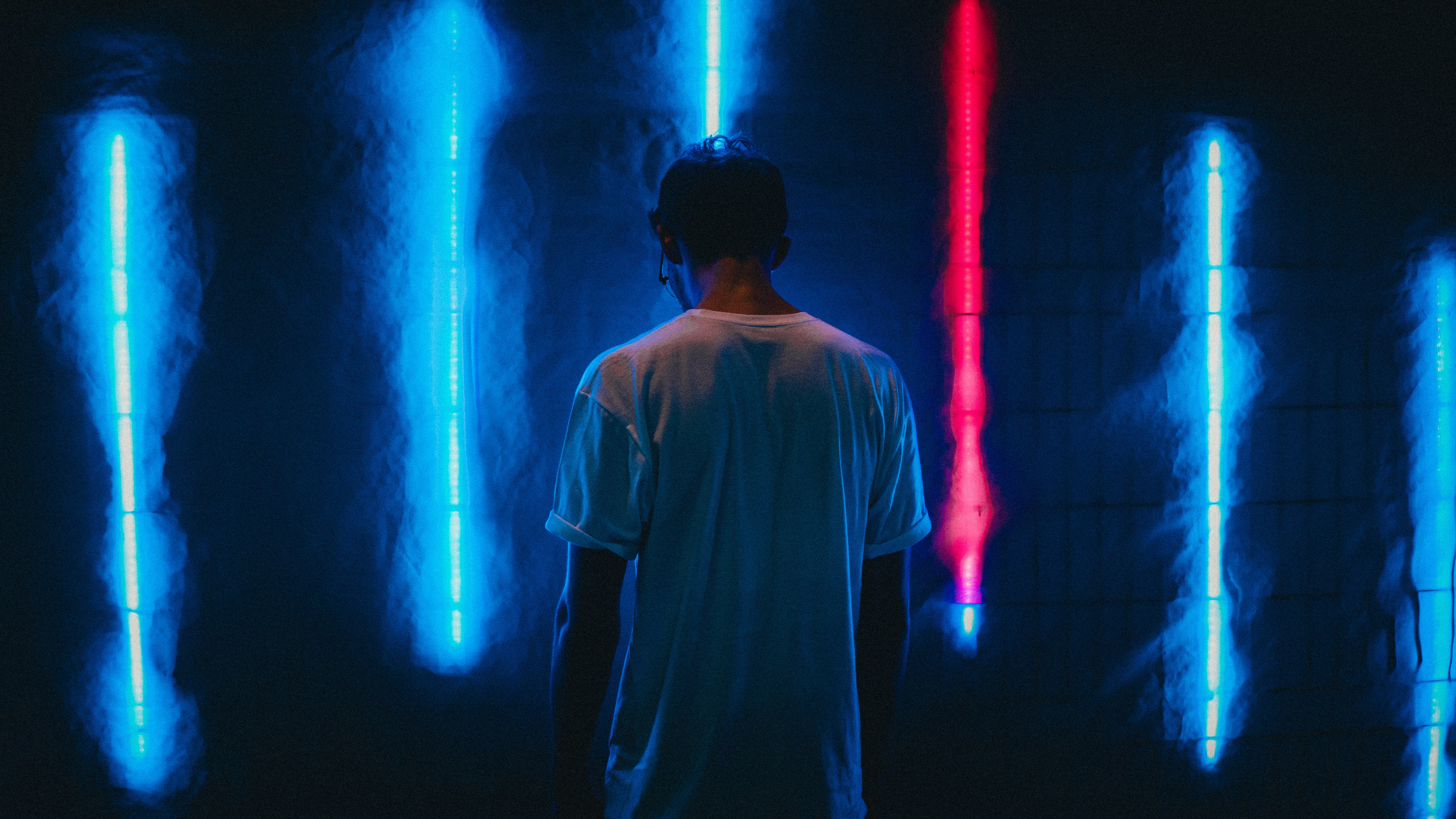 man standing near blue LED strips